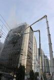 De brandbestrijders pakken een Uitbarsting in een Blok van het Bureau aan Stock Foto's