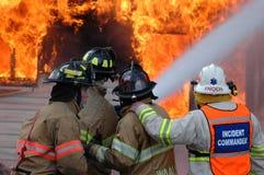 De brandbestrijders vechten een huisbrand Stock Foto