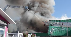 De brandbestrijders vechten de opvlammende commerciële bouw van ladder stock video