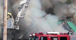 De brandbestrijders vechten de opvlammende commerciële bouw van ladder stock footage