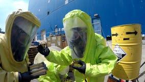De brandbestrijders verzegelen lek van gevaarlijke corrosieve giftige materialen Stock Foto