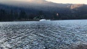 De brandbestrijdershelikopter Erickson neemt water in het meer in een bergbrand boven meer Ghirla in Valganna, Italië stock videobeelden