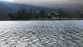 De brandbestrijdershelikopter Erickson neemt water in het meer in een bergbrand boven meer Ghirla in Valganna, Italië stock video