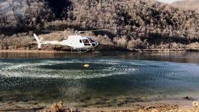 De brandbestrijdershelikopter neemt water in het meer in een bergbrand boven meer Ghirla in Valganna, Italië stock footage