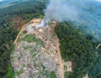De brandbrigade dooft de brand bij de stevig afvalstortplaats stock foto