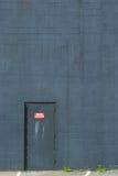 De branddeur van het metaal die in een blauw-grijze bakstenen muur wordt geplaatst Stock Afbeeldingen