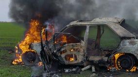 De brandende auto is op het gebied, opgeblazen - omhoog is de auto op brand, brandt de auto in langzame motie stock video