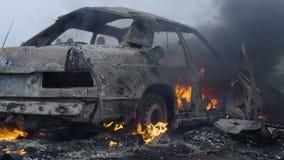 De brandende auto is op het gebied, opgeblazen - omhoog is de auto op brand, brandt de auto in langzame motie stock footage