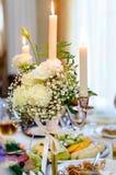 De brandende die kaarsen in een kandelaar, met bloemen wordt verfraaid bevinden zich op een lijst in het restaurant royalty-vrije stock foto