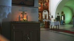 De brandende kaars van de kerkgodsdienst op de achtergrond van het kruis met Jesus stock video