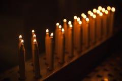 De brandende tribune van gebedkaarsen op een rij Royalty-vrije Stock Afbeelding