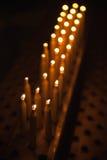 De brandende tribune van gebedkaarsen op een rij Stock Foto's