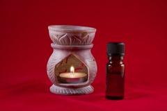 De brander van de olie met fles op rode achtergrond stock fotografie