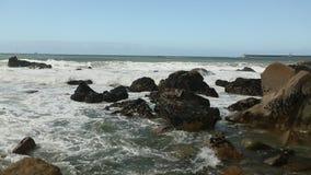 De brandingsplons van de Atlantische Oceaan over de stenen in bewolkt weer stock footage