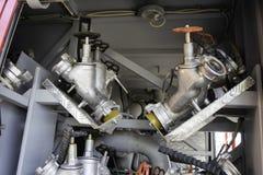De brandlentes worden met drie richtingen opgezet op onderstellen in een compartiment van de brandvrachtwagen stock afbeelding
