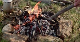 De brandplaats die van de mensenverlichting houten logboeken zetten Echte vriendenmensen openlucht het kamperen tentvakantie in d stock videobeelden