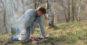 De brandplaats die van de mensenverlichting houten logboeken zetten Echte vriendenmensen openlucht het kamperen tentvakantie in d stock video