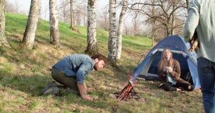 De brandplaats van de mensenverlichting terwijl vriend die houten logboeken brengen Echte vriendenmensen openlucht het kamperen t stock videobeelden