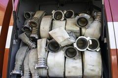 De brandslangen zijn in het compartiment van de brandvrachtwagen stock afbeelding