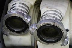 De brandslangen zijn in het compartiment van de brandvrachtwagen, de hoofden dichte omhooggaand van de brandslangverbinding royalty-vrije stock foto