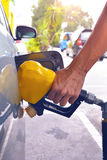 De brandstofpijp van de handholding om gas toe te voegen Stock Foto's