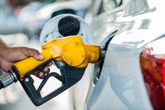 De brandstofvuller vult olie in witte auto Royalty-vrije Stock Afbeeldingen