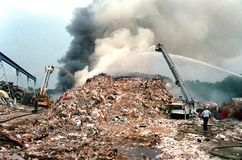 De de brandvrachtwagens en brandbestrijders bestrijden een berg van brand in een grote berg van afval stock afbeeldingen