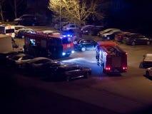 De brandvrachtwagens zijn op de weg met opvlammende lichten bij nacht stock afbeelding
