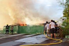 De brandweerlieden en de vrijwilligers op dak doofden brand gebruikend brandslang tijdens huisbrand die binnenlandse barakhuizen  royalty-vrije stock afbeelding
