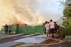 De brandweerlieden en de vrijwilligers op dak doofden brand gebruikend brandslang tijdens huisbrand die binnenlandse barakhuizen  stock afbeeldingen
