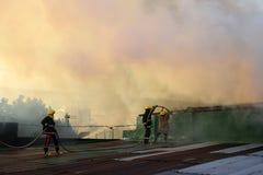 De brandweerlieden en de vrijwilligers op dak doofden brand gebruikend brandslang tijdens huisbrand die binnenlandse barakhuizen  royalty-vrije stock foto's