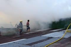 De brandweerlieden en de vrijwilligers op dak doofden brand gebruikend brandslang tijdens huisbrand die binnenlandse barakhuizen  royalty-vrije stock afbeeldingen