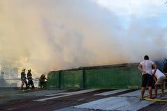 De brandweerlieden en de vrijwilligers op dak doofden brand gebruikend brandslang tijdens huisbrand die binnenlandse barakhuizen  stock foto