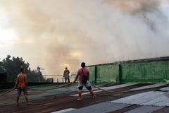 De brandweerlieden en de vrijwilligers op dak doofden brand gebruikend brandslang tijdens huisbrand die binnenlandse barakhuizen  royalty-vrije stock foto