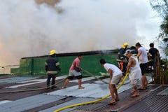 De brandweerlieden en de vrijwilligers op dak doofden brand gebruikend brandslang tijdens huisbrand die binnenlandse barakhuizen  stock afbeelding