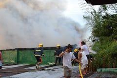 De brandweerlieden en de vrijwilligers op dak doofden brand gebruikend brandslang tijdens huisbrand die binnenlandse barakhuizen  royalty-vrije stock fotografie