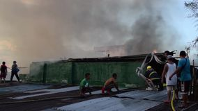 De brandweerlieden en de vrijwilligers verzamelen zich op dak gedoofde brand gebruikend brandslang tijdens huisbrand die binnenla stock footage