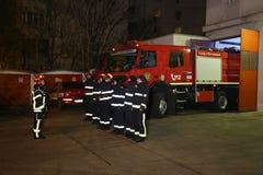 De brandweerlieden van de brandvrachtwagen klaar voor actie Stock Afbeelding