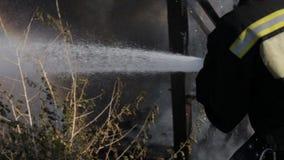 De brandweerman dooft de brand met een waterstraal stock video