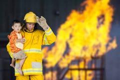 De brandweerman redde het kind van de brand Stock Foto