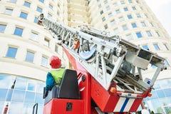 De brandweerman tijdens dooft een brand Royalty-vrije Stock Foto's