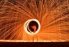 De brandweerman toont op de mens van de stranddans het jongleren met met swing fire spa stock afbeelding