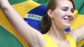 De Braziliaanse Jonge Vrouw viert het houden van de vlag van Brazilië in Langzame Motie royalty-vrije stock foto