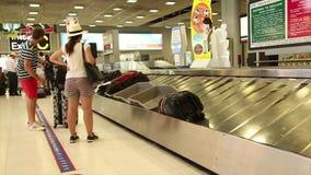 De brede geschotene passagiers wachten op hun bagage bij bagageband na een interna stock video