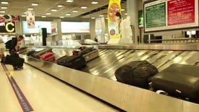 De brede geschotene passagiers wachten op hun bagage bij baggaeeis na een internationale vlucht in Azië stock video