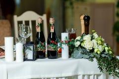 De brede witte kaars en twee groene flessen met rode wijndecorum Royalty-vrije Stock Foto