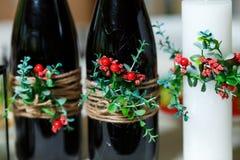 De brede witte kaars en twee groene flessen met rode wijndecorum Stock Foto's