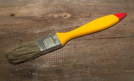 De breedte van de verfborstel 1 duim met geel handvat op een houten achtergrond Stock Foto