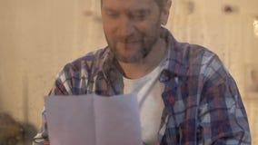 De brief van de mensenlezing achter nat venster, zonstralen die, geloof in beter, hoop glanzen stock video