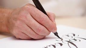De brieven van de Calligraphisttekening op witte spatie Dicht schot Front View Het kalligrafische van letters voorzien Bemant han stock videobeelden